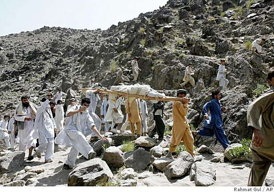 Locals carry the dead body who is believed to be a Japanese male in Bodyalai village of Khiva district in Nangarhar province, east of Kabul, Afghanistan, Wednesday, Aug 27, 2008. A body that appeared to be Japanese was found Wednesday by searchers in Afghanistan looking for a kidnapped aid worker, Japan's Foreign Ministry said.(AP Photo/Rahmat Gul) Photo: Rahmat Gul, AP