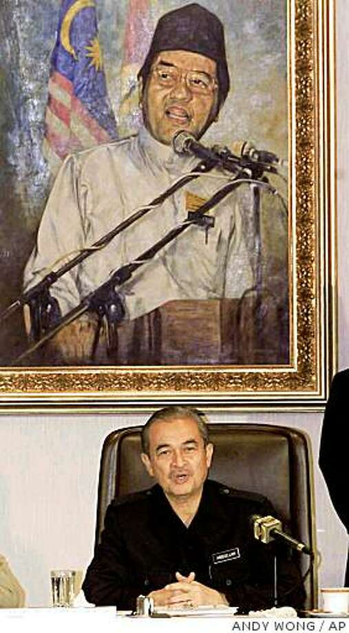 With the Prime Minister Mahathir Mohamad's portrait at the backdrop, Malaysia's Deputy Prime Minister Abdullah Badawi speaks during a news conference after chairing the United Malays National Organization (UMNO) Supreme Council meeting at the headquarters in Kuala Lumpur, Malaysia, Tuesday, June. 25, 2002. Photo: ANDY WONG, AP