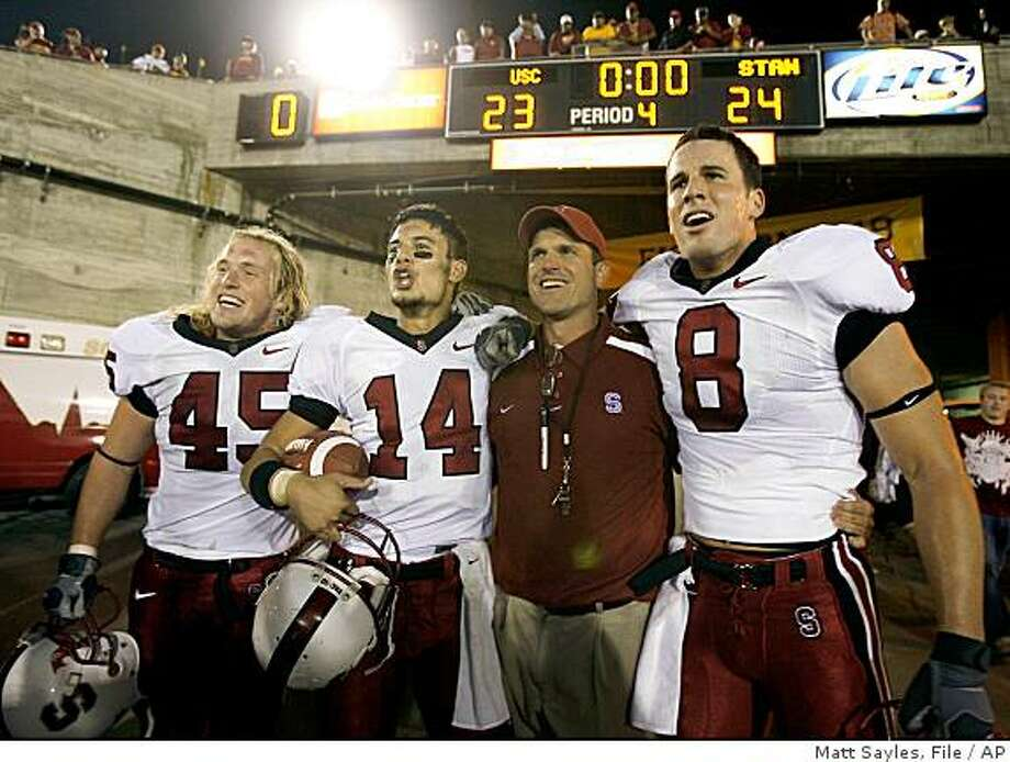 ** FILE ** In this Oct. 6, 2007, file photo, from left, Stanford's Ben Ladner, Tavita Pritchard, coach Jim Harbaugh, and Evan Moore celebrate after Stanford upset Southern California 24-23 in a football game in Los Angeles. In just one season, Harbaugh turned Stanford from a team that flirted with a winless season into one that could challenge and even beat the top teams in the country. (AP Photo/Matt Sayles, File) Photo: Matt Sayles, File, AP