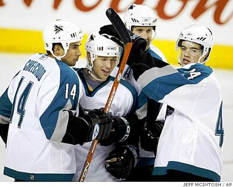 San Jose Sharks' Mark Smith, center, celebrates his goal with teammates, from left, Jonathan Cheechoo, Joe Thornton, and Marc-Edouard Vlasic, during third period NHL hockey action against the Calgary Flames in Calgary, Monday, Oct. 9, 2006. The Sharks beat the Flames 4-1. (AP PHOTO/CP, Jeff McIntosh) Photo: JEFF MCINTOSH, AP