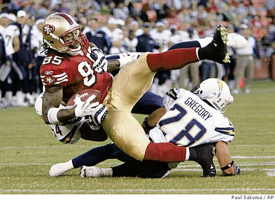 San Francisco 49ers tight end Vernon Davis (85) is tackled by San Diego Chargers linebacker Stephen Cooper, in back, and Steve Gregory, right, in the second quarter of their preseason NFL football game in San Francisco, Friday, Aug. 29, 2008. (AP Photo/Paul Sakuma) Photo: Paul Sakuma, AP