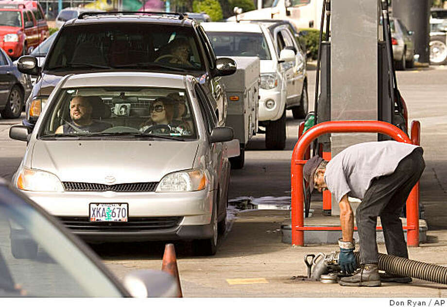 Cars line up for gas as a tanker truck driver fills the station underground tanks in Troutdale, Ore., Friday, Aug. 29, 2008.  Retail gas prices swung higher Friday _ the first increase in 43 days _ as analysts warned that a direct hit on U.S. energy infrastructure by Tropical Storm Gustav could send pump prices hurtling toward $5 a gallon. (AP Photo/Don Ryan) Photo: Don Ryan, AP