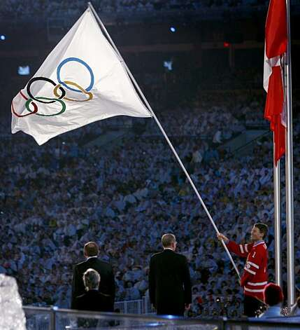 Vancouver Mayor Gregor Robertson (right) waves the Olympic flag one last time before returning it to IOC President Jacques Rogge during the traditional flag handover ceremony at the Closing Ceremonies of the Winter Olympic Games in Vancouver, British Columbia, on Sunday, Feb. 28, 2010. Photo: Paul Chinn, The Chronicle