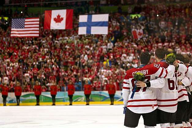 Canada's Sidney Crosby watches as the flag are raised after team Canada recieved their gold medals after winning the men's ice hockey gold medal game at the 2010 Winter Olympics on Sunday, Feb. 28, 2010, in Vancouver. Canada won the game 3-2 on a goal by Canada's Crosby. ( Smiley N. Pool / Houston Chronicle) Photo: Smiley N. Pool, Chronicle Olympic Bureau