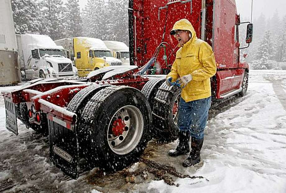 Mark Verloop, of Reno, chains up his big rig at the Tesoro truck stop in Dutch Flat, Calif. on Wednesday Mar. 3, 2010, as a heavy snow stormsmoves through the area. Wednesday's monthly snow survey is likely to show that the water content of the Sierra snowpack is above average for this time of year. Photo: Michael Macor, The Chronicle