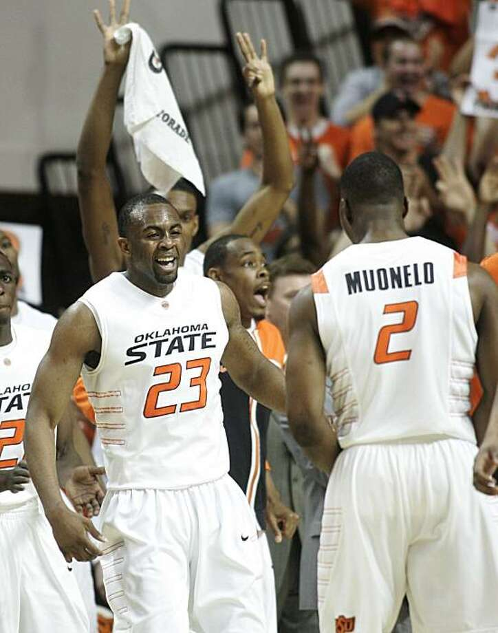 Oklahoma State guard James Anderson, left, smiles and celebrates with teammate guard Obi Muonelo, right, during a time out in the first half of an NCAA college basketball game against No. 1 Kansas in Stillwater, Okla., Saturday, Feb. 27, 2010. Oklahoma State won 85-77. Photo: Sue Ogrocki, AP