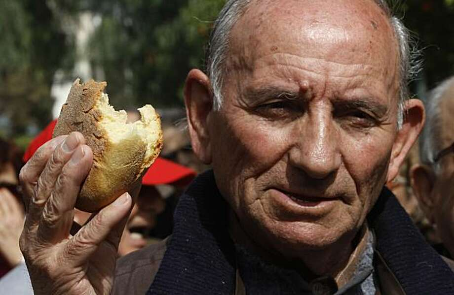 A pensioner holds bread as he shouts slogans during a demonstration outside Prime minister's office in central Athens, Greece, on Wednesday, March 3, 2010.Greece announced painful new austerity measures Wednesday worth euro4.8 billion (US$6.5 billion) insavings to deal with an unprecedented financial crisis that has hammered the euro and driven up Greece's cost of borrowing. Photo: Petros Giannakouris, AP