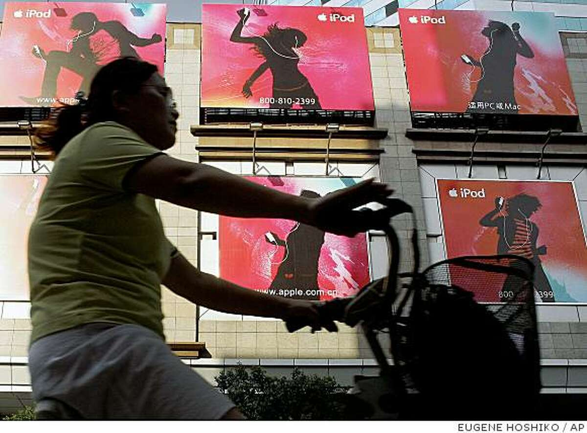 ** FILE ** A woman rides a bicycle past advertisements of Apple Computer's iPod in this Friday, Aug. 18, 2006 file photo in Shanghai, China. Apple Computer said Wednesday, Aug. 30, 2006, it was working to resolve a dispute over alleged labor abuses by an iPod manufacturer in China. Hongfujin Precision Industry Co., a major exporter owned by a Taiwanese company, filed a defamation lawsuit against two journalists at the state-run newspaper China Business News who ran stories alleging that workers on iPod assembly lines worked under harsh conditions for low pay. (AP Photo/Eugene Hoshiko, FILE)Ran on: 08-31-2006A woman rides a bicycle past an iPod ad in Shanghai. A Chinese iPod manufacturer has been criticized over alleged labor abuses.Ran on: 11-14-2007A woman pedals past Apple ads in Shanghai. An iPhone deal would give Apple an enormous market. ** FILE ** A woman rides a bicycle past advertisements of Apple Computer's iPod in this Friday, Aug. 18, 2006 file photo in Shanghai, China. Apple Computer said Wednesday, Aug. 30, 2006, it was working to resolve a dispute over alleged labor abuses by an iPod manufacturer in China. Hongfujin Precision Industry Co., a major exporter owned by a Taiwanese company, filed a defamation lawsuit against two journalists at the state-run newspaper China Business News who ran stories alleging that workers on iPod assembly lines worked under harsh conditions for low pay. (AP Photo/Eugene Hoshiko, FILE) Ran on: 08-31-2006 A woman rides a bicycle past an iPod ad in Shanghai. A Chinese iPod manufacturer has been criticized over alleged labor abuses. Ran on: 11-14-2007 A woman pedals past Apple ads in Shanghai. An iPhone deal would give Apple an enormous market.