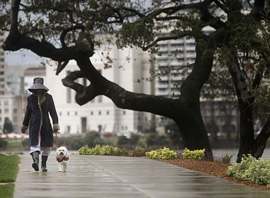 Mattie Walls and her Maltese mix, Chay, take their morning walk around Lake Merritt as rains intermittently falls on Tuesday March 02, 2010 in Oakland, Calif. Photo: Mike Kepka, The Chronicle