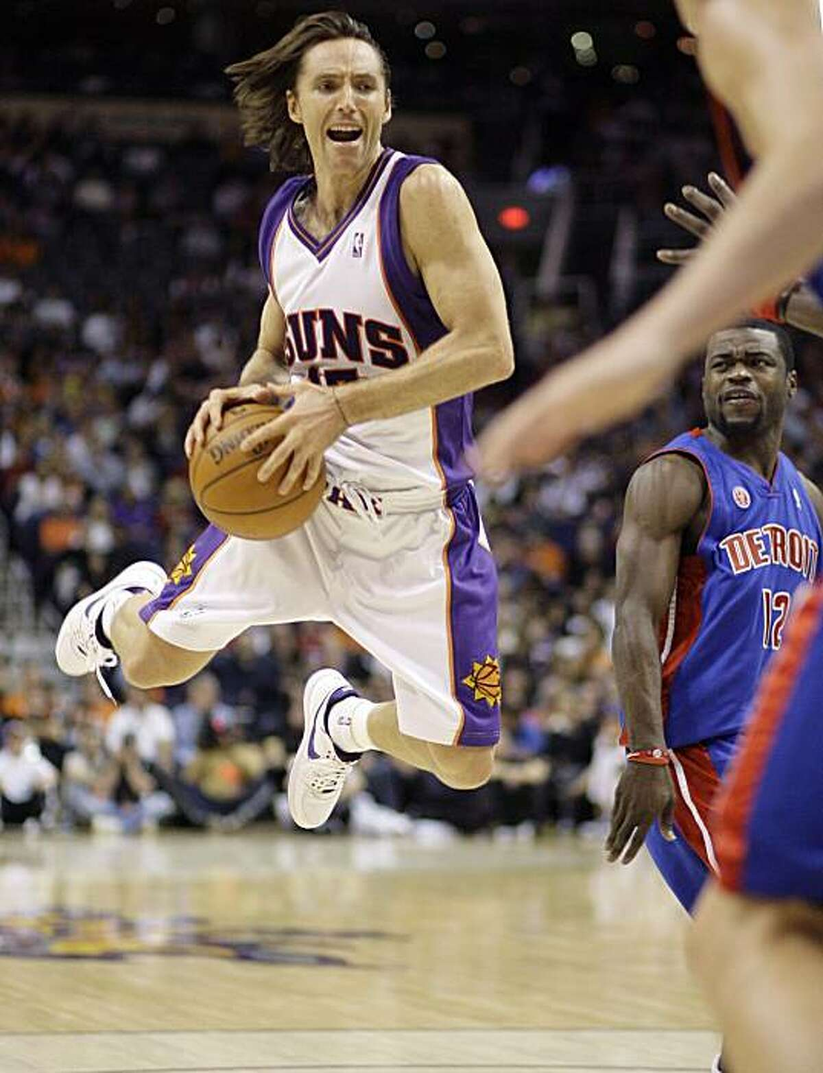 Phoenix Suns guard Steve Nash, left, reacts to being fouled by Detroit Pistons guard Will Bynum, right, during the third quarter of an NBA basketball game Sunday, Nov. 22, 2009, in Phoenix. The Suns won 117-91. (AP Photo/Paul Connors)
