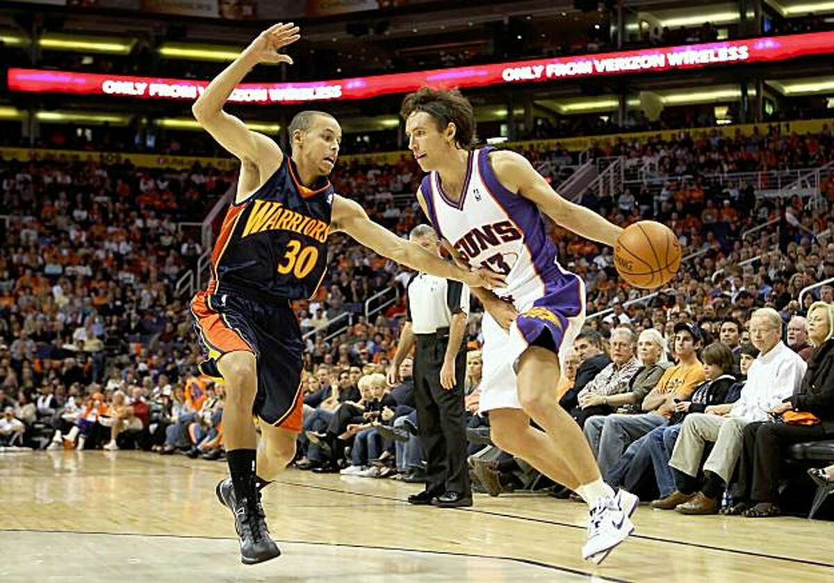 Steve Nash of the Phoenix Suns handles the ball under pressure from Stephen Curry of the Golden State Warriors.