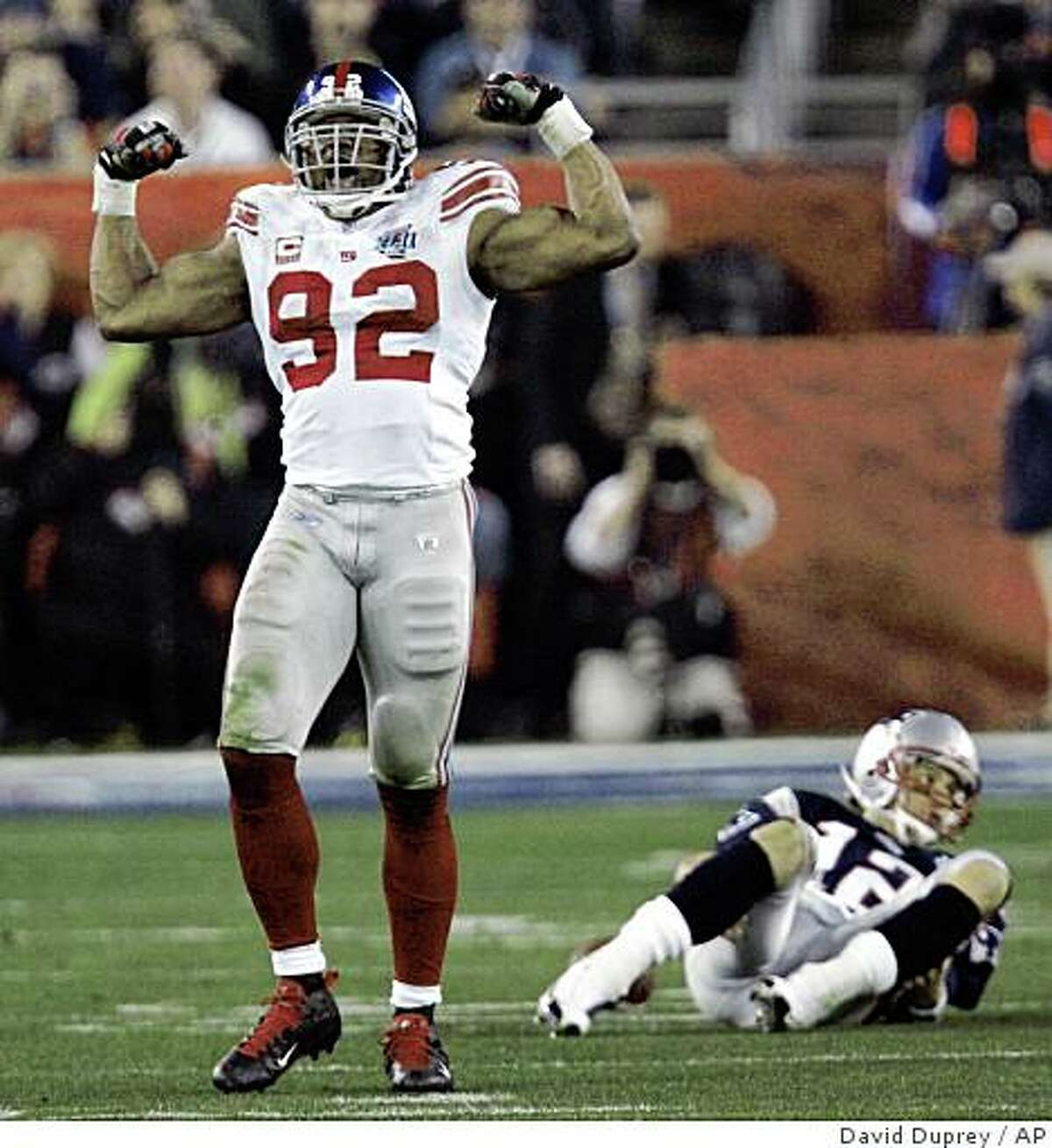 ** FILE ** In this Feb. 3, 2008 file photo, New York Giants defensive end Michael Strahan (92) reacts after sacking New England Patriots quarterback Tom Brady (12) in the third quarter during the Super Bowl XLII football game at University of Phoenix Stadium in Glendale, Ariz. Seven-time Pro Bowl defensive end Michael Strahan is retiring after a 15-year career, capped by a Super Bowl title with the New York Giants in February. The 36-year-old Strahan, the NFL's active leader in sacks, informed the Giants on Monday June 9, 2008. (AP Photo/David Duprey, File)