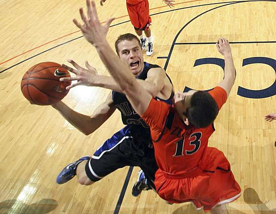 Duke's Jon Scheyer shoots in front of Virginia's Sammy Zeglinski (13) during an NCAA college basketball game Sunday Feb. 28, 2010 in Charlottesville, Va. Duke won 67-49. Photo: Andrew Shurtleff, AP