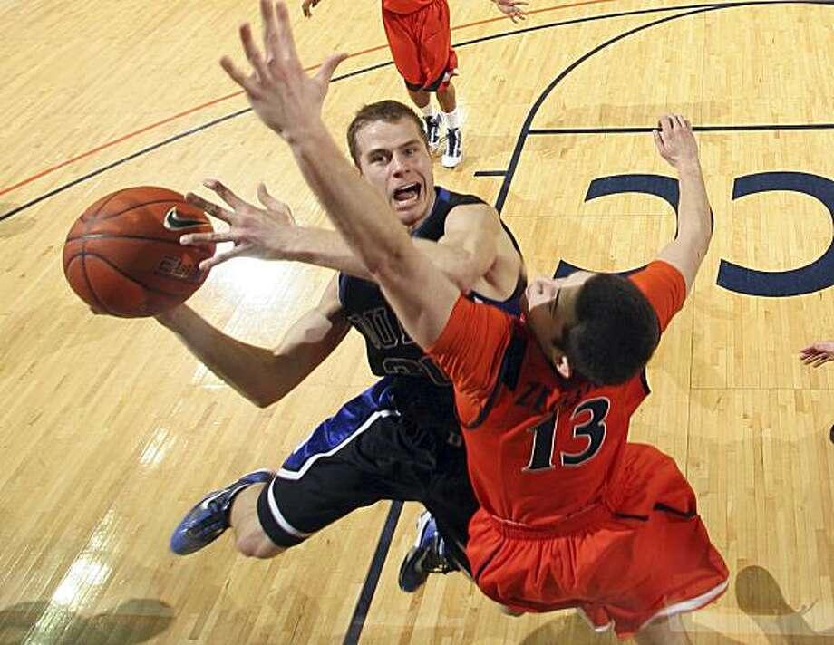 Duke's Jon Scheyer shoots in front of Virginia's Sammy Zeglinski (13) during an NCAA college basketball game Sunday Feb. 28, 2010 in Charlottesville, Va. Duke won 67-49. Photo: Andrew Shurtleff, AP