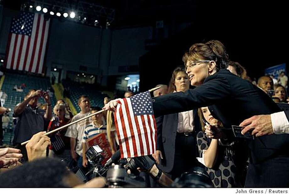 Alaska Governor Sarah Palin takes a flag from a supporter after being chosen the Republican vice presidential running mate for U.S. Republican presidential candidate Senator John McCain (R-AZ) at a campaign event in Dayton, Ohio August 29, 2008. REUTERS/John Gress (UNITED STATES) US PRESIDENTIAL CAMPAIGN 2008 (USA) Photo: John Gress, Reuters