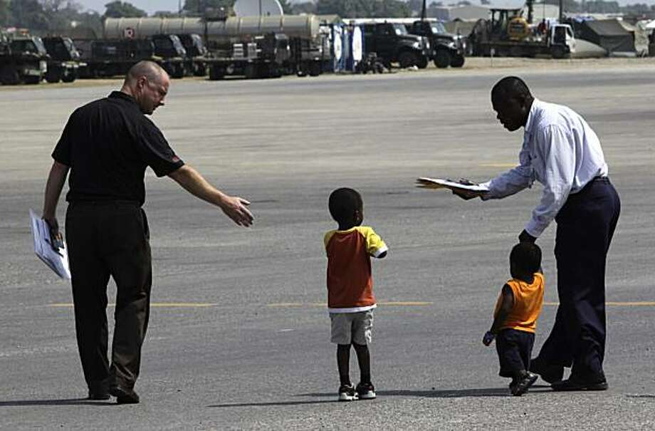 Orphaned children accompanied by unidentified men walk in the tarmac towards a US-bound plane at the airport in Port-au-Prince, Wednesday Feb. 24, 2010. Six Haitian orphans boarded the airplane to be united with their adopted parents four days after Haitian police seized them out of fear they were being kidnapped. Photo: Ramon Espinosa, AP