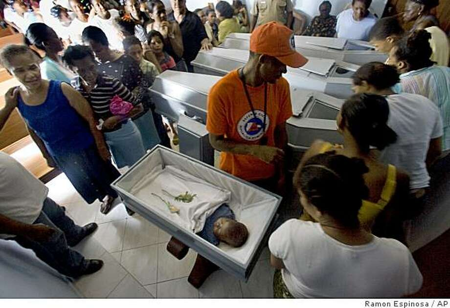 Residents attend the funeral of the victims of a landslide caused by Hurricane Gustav at the Guachupita neighborhood in Santo Domingo, Wednesday, Aug. 27, 2008. Authorities said that eight people died, including two infants, in the landslide.(AP Photo/Ramon Espinosa). Photo: Ramon Espinosa, AP