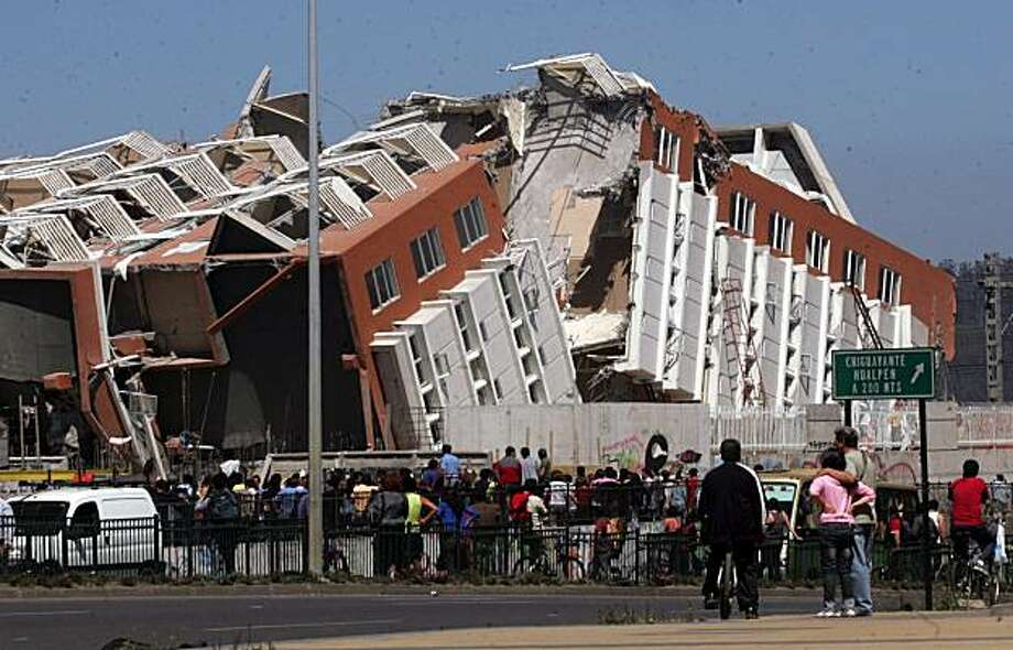 Residents look at a collapsed  building in Concepcion, Chile, Saturday Feb. 27, 2010 after an 8.8-magnitude struck central Chile. The epicenter was 70 miles (115 kilometers) from Concepcion,  Chile's second-largest city. Photo: Str, AP