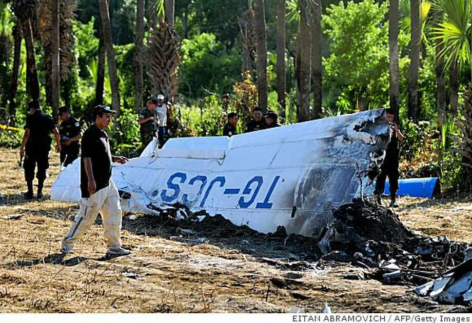 An aerial investigator looks at the wing of a light aircraft that crashed in the village El Puente, Cabanas municipality, Teculutan department, some 110 km east of Guatemala City on August 24, 2008. At least ten out of 14 tourists died when the light aircraft crashed for unknown reasons. Five of the tourists killed were American and the other five Guatemalan. AFP PHOTO/Eitan Abramovich (Photo credit should read EITAN ABRAMOVICH/AFP/Getty Images) Photo: EITAN ABRAMOVICH, AFP/Getty Images