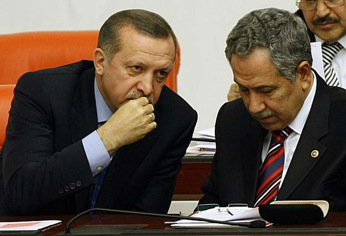 Turkish Prime Minister Recep Tayyip Erdogan, left, and his deputy Bulent Arinc, right, speak during a debate at the parliament, after a meeting between President Abdullah Gul, Erdogan and Chief of Staff Gen. Ilker Basbug in Ankara, Turkey, Thursday, Feb. 25, 2010. A Turkish court in Istanbul on Thursday charged more ranking military officers with plotting to topple the Islamic-rooted government, increasing the number of jailed officers to 20 _ including five admirals and three generals. The court acted hours before Gul, Gen. Basbug and Erdogan met to discuss tensions over the largest-ever crackdown on the military in Turkey.( AP Photo/Burhan Ozbilici)