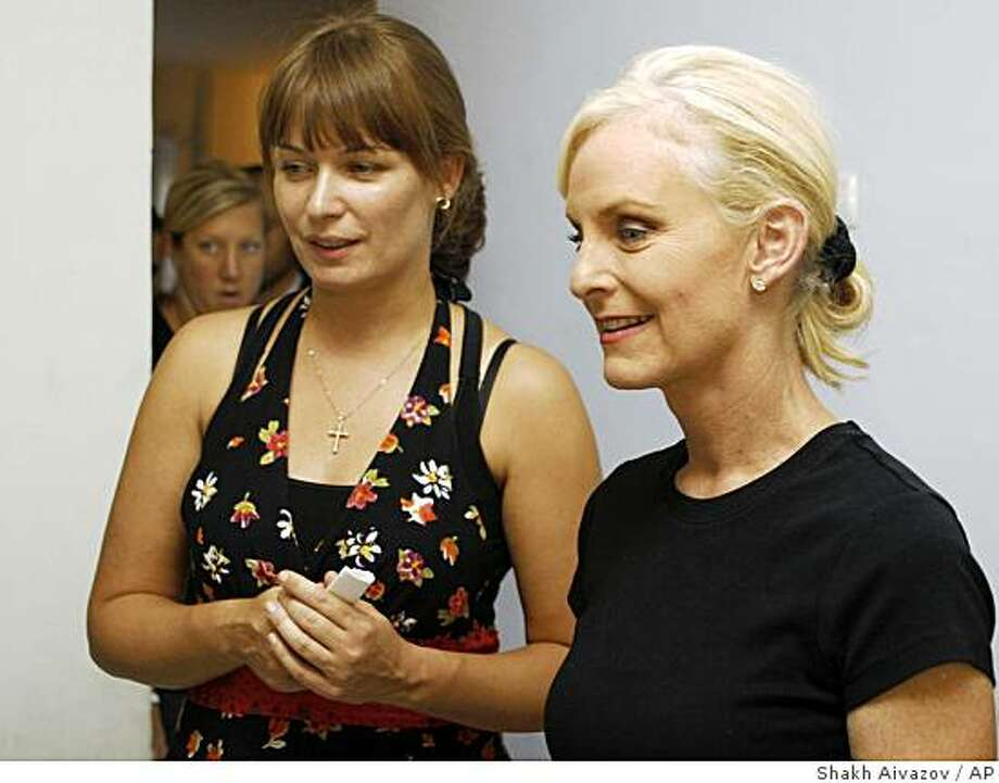 "Sandra Roeloefs, left, the wife of Georgian President Mikhail Saakashvili, accompanies Cindy McCain, right, the wife of U.S. presidential candidate John McCain, at a refugee center in Tbilisi, Georgia, Tuesday, Aug. 26, 2008. McCain visited refugees at a center in the capital Tbilisi on Tuesday. She lamented that they couldn't go home because ""of the situation that the Russians have caused."" (AP Photo/Shakh Aivazov) Photo: Shakh Aivazov, AP"