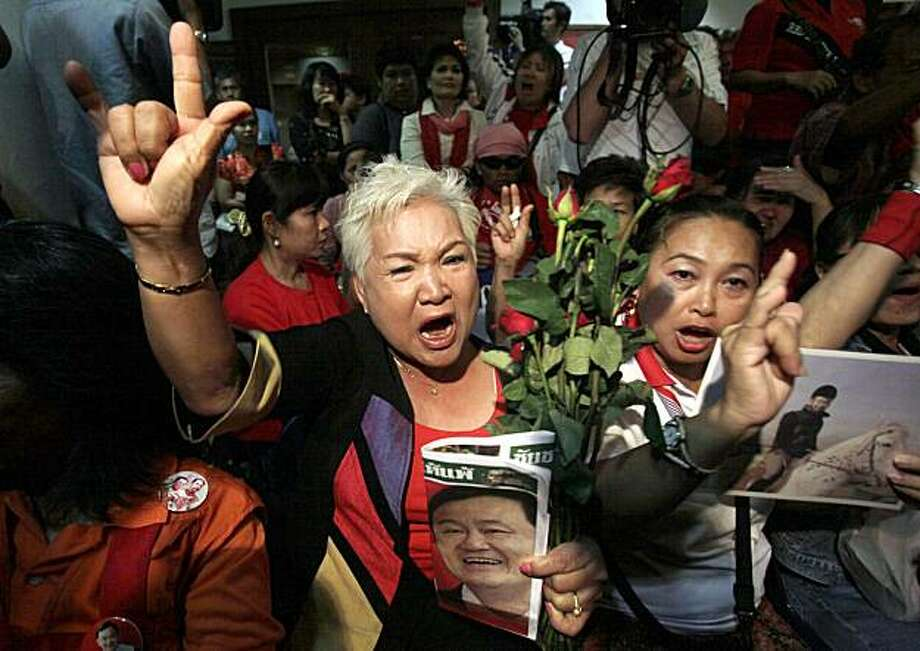 Supporters of deposed Prime Minister Thaksin Shinawatra shout slogans at Pheu Thai Party in Bangkok, Thailand, on Friday, Feb. 26, 2010. Thailand's highest court has ruled that Thaksin concealed his assets while in office and abused his power for personalgain, and ordered the seizure of 46 billion baht (US$1.4 billion) of his US$2.29 billion in frozen assets. Photo: Sakchai Lalit, AP