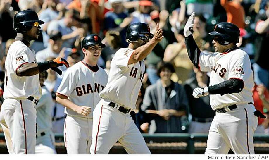 San Francisco Giants' Bengie Molina. right, is greeted at plate by teammates Randy Winn, center, and Fred Lewis, far left, after hitting a three-run home run off San Diego Padres relief pitcher Mike Adams in the seventh inning of a baseball game in San Francisco, Sunday, Aug. 24, 2008. (AP Photo/Marcio Jose Sanchez) Photo: Marcio Jose Sanchez, AP