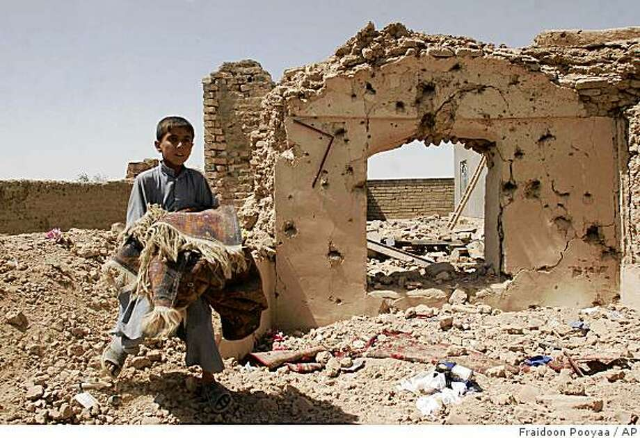 A boy carries his belongings next to the rubble of his home which was destroyed in a U.S. airstrike in the villiage of Azizabad in the Shindand district of Herat province, Afghanistan, Saturday, Aug 23, 2008. The U.S.-led coalition said Saturday that it would investigate allegations of civilian deaths during a battle in western Afghanistan.  Afghanistan's Ministry of Interior says that 76 civilians were killed in strikes in the Shindand district of Herat province. U.S. coalition officials say that Thursday's strikes killed 30 militants, including a Taliban leader. (AP Photo/Fraidoon Pooyaa) Photo: Fraidoon Pooyaa, AP