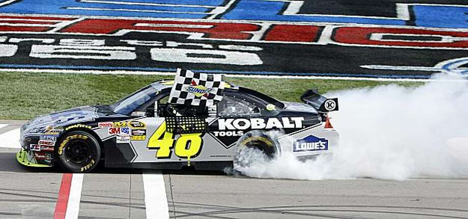 Jimmie Johnson (48) holes a checkered flag and does a burnout after winning the NASCAR Sprint Cup Series auto race Sunday, Feb. 28, 2010, in Las Vegas. Photo: Isaac Brekken, AP