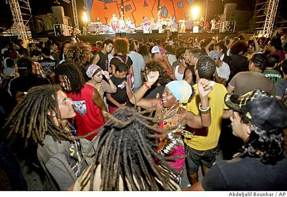 **APN ADVANCE FOR SUNDAY AUG. 24**   Moroccans dances during Jamaican singer Burning Spear Concert, Saturday July 19, 2008, in Casablanca Morocco. Concerts and dozens of festivals are part of policy by Moroccan authorities to promote liberal culture and diversity in the country. (AP Photo/Abdeljalil Bounhar) Photo: Abdeljalil Bounhar, AP