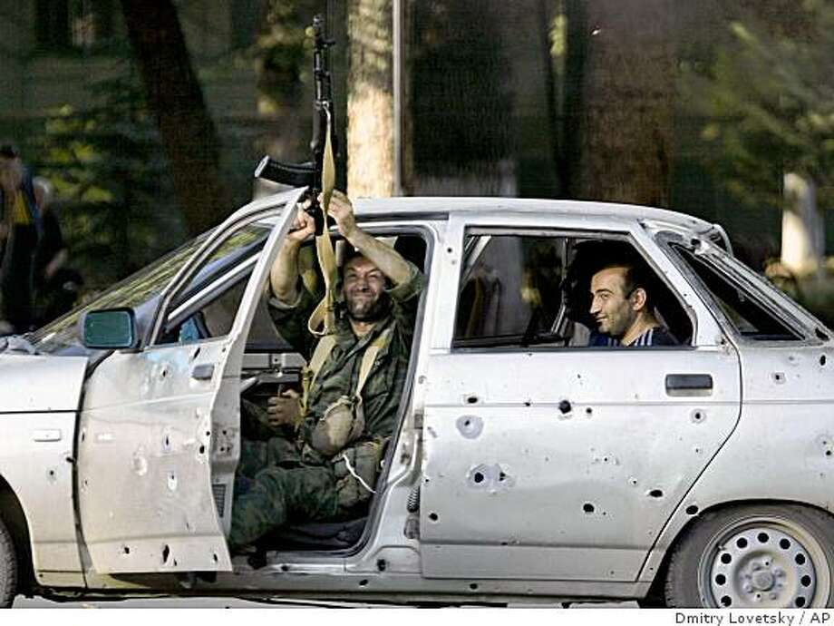 A South Ossetian prepares to fire his weapon while riding in a bullet-ridden car in Tskhinvali, the capital of Georgia's separatist-controlled territory of South Ossetia, Tuesday, Aug. 26, 2008, as they celebrate Russian President Dmitry Medvedev signing a decree recognizing the independence of the breakaway Georgian territories of South Ossetia and Abkhazia. (AP Photo/Dmitry Lovetsky) Photo: Dmitry Lovetsky, AP