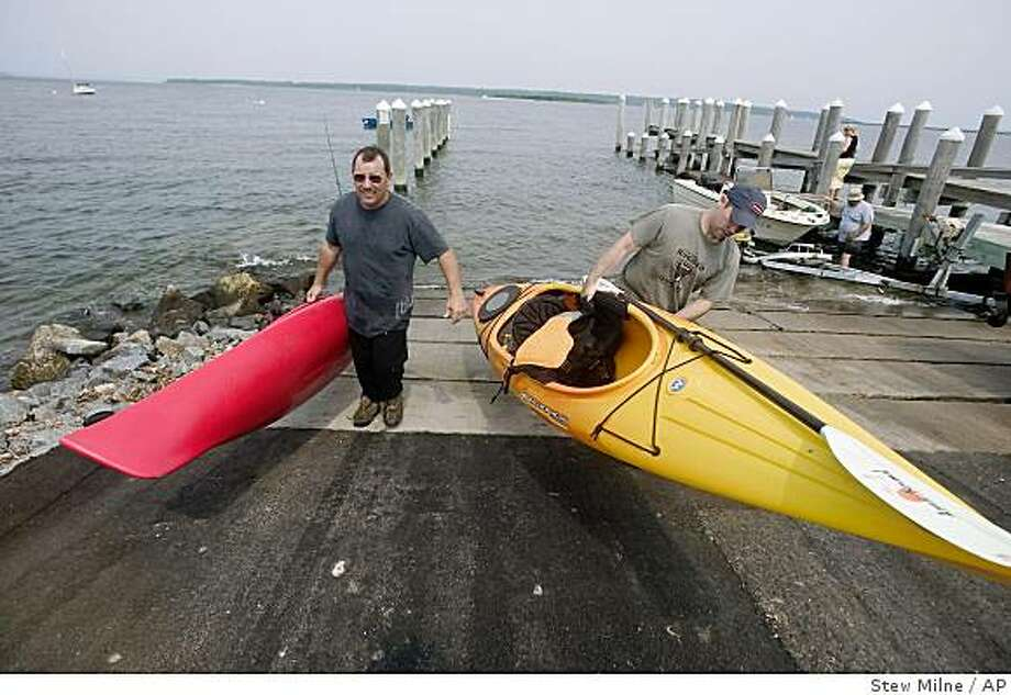 Frank Charette Jr., left and his son Frank Charett III, lift their kayaks out of Narragansett Bay after kayaking to Portsmouth, R.I., Sunday July 20, 2008. The Blue Trail, a 10-mile coastal path that hugs the shoreline of Aquidneck Island, will eventually run from Portsmouth to Newport. (AP Photo/Stew Milne) Photo: Stew Milne, AP