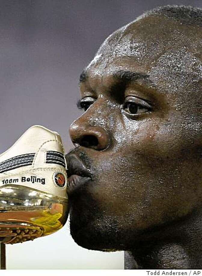 Jamaica's Usain Bolt kisses his shoe after winning the gold in the men's 100-meter final. Photo: Todd Andersen, AP