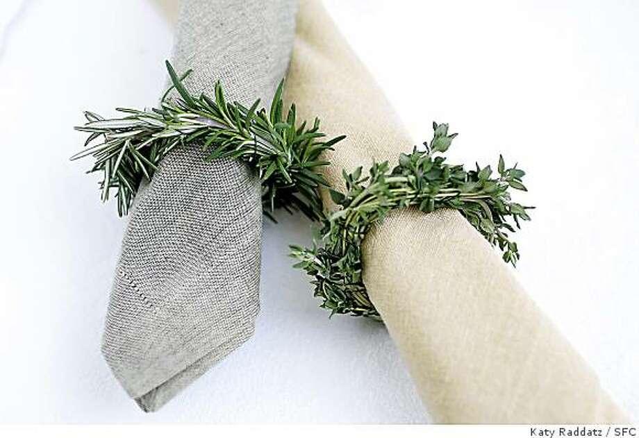 Rosemary and thyme napkin rings on rolled linen napkins. Photo: Katy Raddatz, SFC