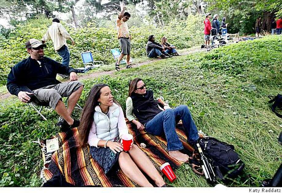 Kirk Sands, left, Dede Weadock, center, and Monique Laliberte, right, seated on the bank of Metson Lake outside the perimeter fence of the Outside Lands concert, listen to the music of Toots and the Maytals while Matt Zito and Greg Phillips play air guitar behind them, at the Outside Lands concert in Golden Gate Park in San Francisco, Calif. on Sunday, August 24, 2008. Photo: Katy Raddatz