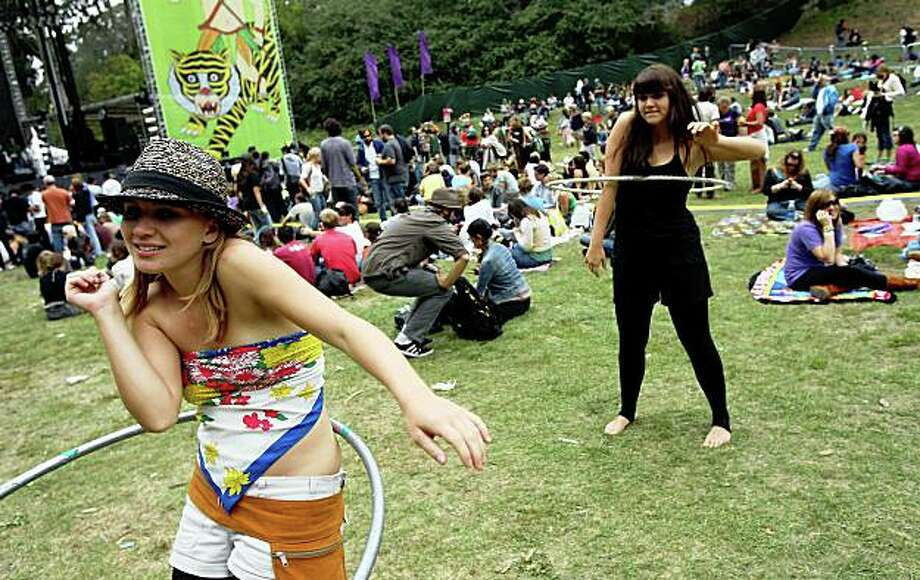 Amy Serrano (left) and her sister Christy Serrano, visiting from Huntington Beach, brought hula hoops to entertain themselves between acts at the Outside Lands Music and Arts Festival in Golden Gate Park in San Francisco, Calif., on Saturday, August 23, 2008. Photo: Laura Morton, Special To The Chronicle