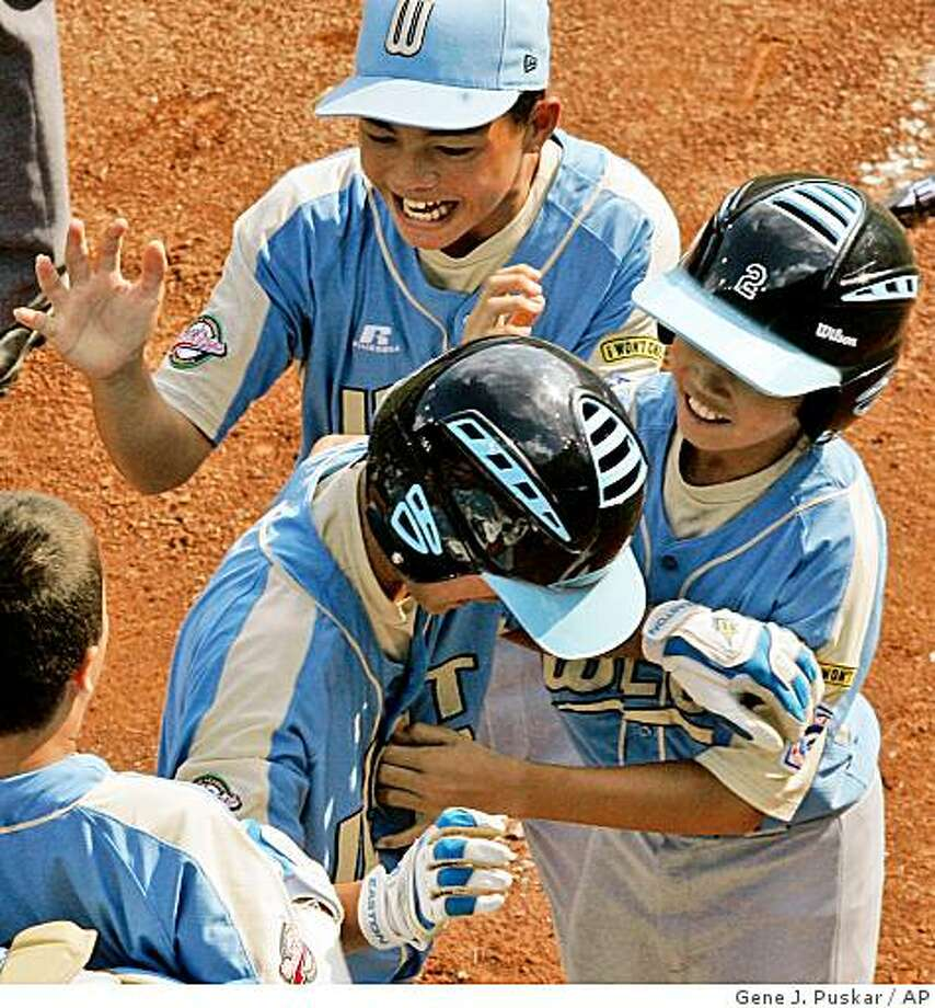 Waipahu, Hawaii's Tanner Tokunaga, center, is welcomed by teammates Jedd Andrade, top left, and Kainoa Fong (2) after hitting a second-inning, two-run homer off Matamoros, Mexico, pitcher Sergio Rodriguez in the Little League World Series championship baseball game in South Williamsport, Pa., Sunday, Aug. 24, 2008. Tokunaga homered twice in Hawaii's 12-3 win. (AP Photo/Gene J. Puskar) Photo: Gene J. Puskar, AP