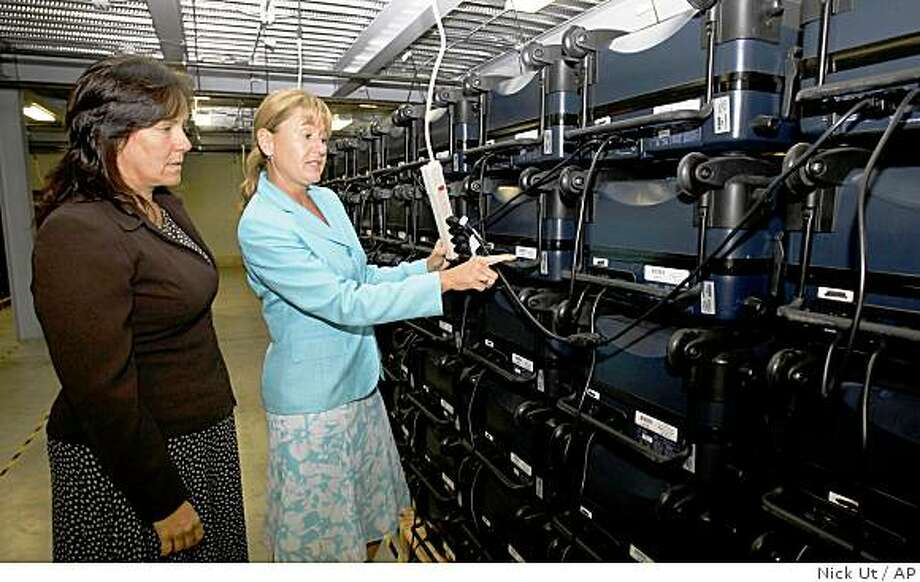 Kathi Payne, left, electronic analyst and Kari Verjil, elections director for Riverside County pose at the Registrar of Voters warehouse with thousands of mothballed touch-screen voting machines on Tuesday Aug. 19, 2008 in San Bernardino, Calif. The machines were entombed by disenchanted state officials who'd once embraced the new technology, only to see elections delayed by vanishing votes, breakdowns, malfunctions and increasing evidence that the ATM-like devices were vulnerable to hackers. (AP Photo/Nick Ut) Photo: Nick Ut, AP