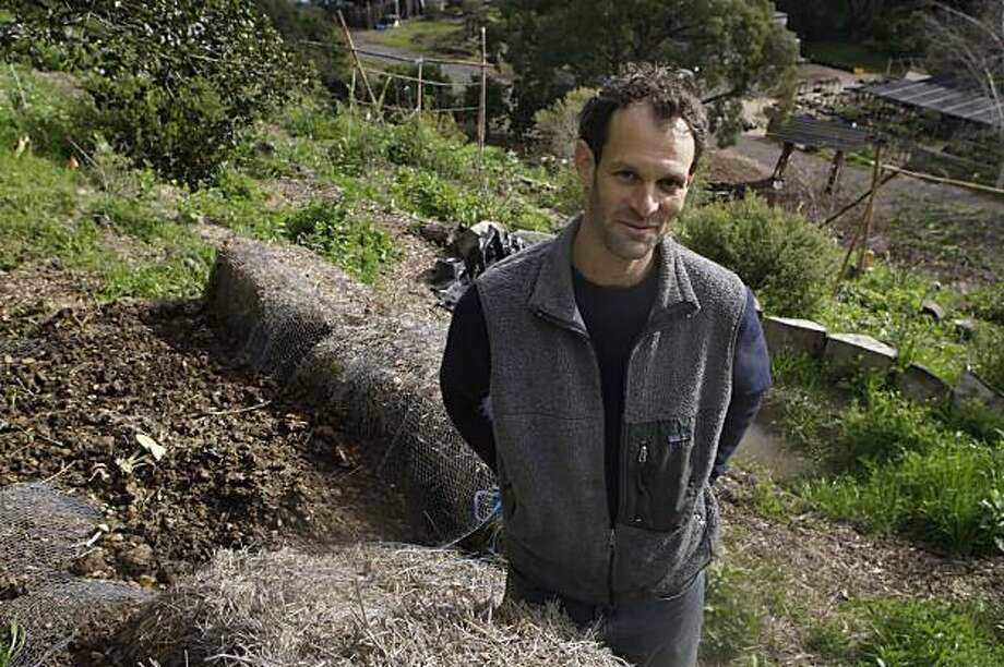 Chris Shein of Merritt College's Landscape Horticulture Department is seen at the school's one acre garden on Wednesday February 10, 2010 in Oakland, Calif. Shein stands next to bales of hay and manure which have been constructed into a planter which will naturally decompose and turn into soil. Photo: Lea Suzuki, The Chronicle