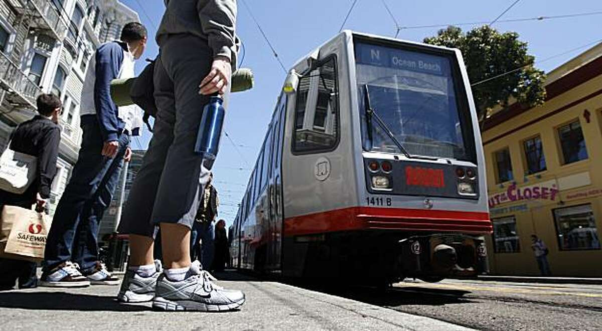 MUNI passengers wait for the light rail train on Duboce Street at Church in San Francisco Tuesday August 4, 2009