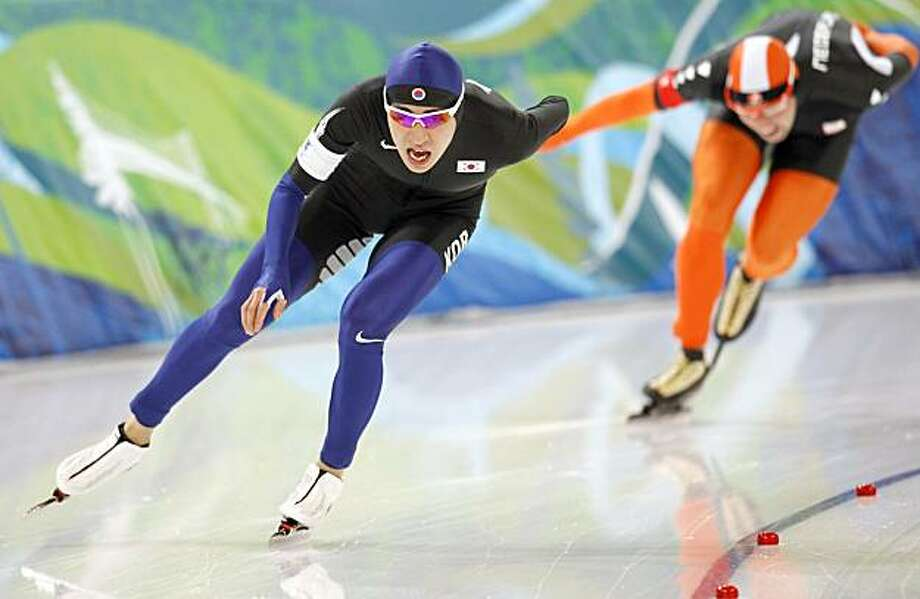 New Olympic record holder Korea's Lee Seung-Hoon, left, passes in the same lane as he overtakes Netherlands's Arjen van de Kieft, right, during the men's 10,000 meter speed skating race at the Richmond Olympic Oval at the Vancouver 2010 Olympics in Vancouver, British Columbia, Tuesday, Feb. 23, 2010. Photo: Kevin Frayer, AP