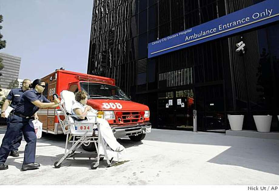 Los Angeles Fire Department paramedics drop off a woman at the emergency entrance at Century City Doctors Hospital Friday, August 22, 2008 in Los Angeles. Officials say the struggling Century City Doctors Hospital is filing for Chapter 7 bankruptcy protection and will shut its doors by Aug. 29 saying in a statement Friday that it has canceled all elective surgeries and will close its emergency department at noon Saturday. (AP Photo/Nick Ut) Photo: Nick Ut, AP