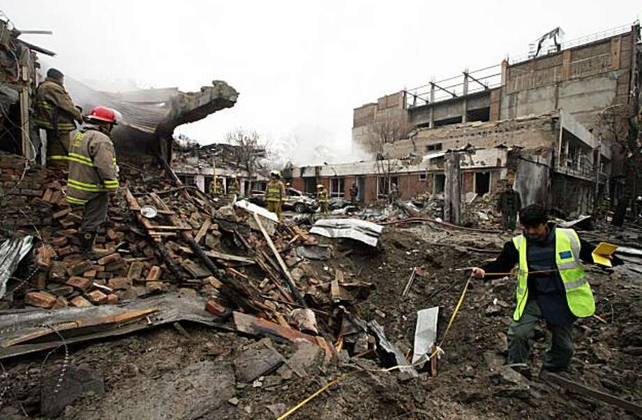 An Afghan police investigator measures a crater left behind after a car bomb exploded outside a small guest house used by foreigners in central Kabul on Friday, February 26, 2010. The blast was followed by smaller explosions and sporadic gunfire as police searched the area for the attackers. Medical officials said nine people were killed. (Dion Nissenbaum/MCT) Photo: Dion Nissenbaum, MCT