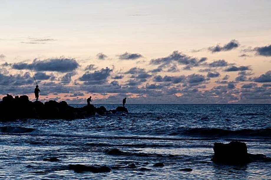 Fisherman at sunset -- the view from the beach in front of Mama's Fish House. Photo: John Flinn, Special To The Chronicle
