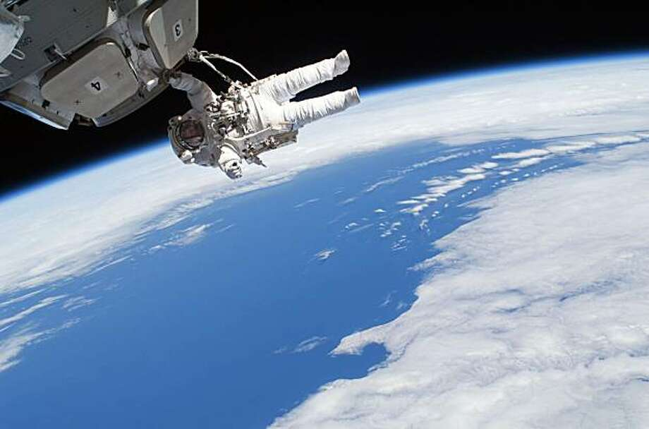In this image provided by NASA, astronaut Nicholas Patrick participates in extravehicular activity as construction and maintenance continue on the International Space Station. During the spacewalk, Patrick and fellow astronaut Robert Behnken removed insulation blankets and launch restraint bolts from each of the Cupola's seven windows. Photo: Nasa, AP