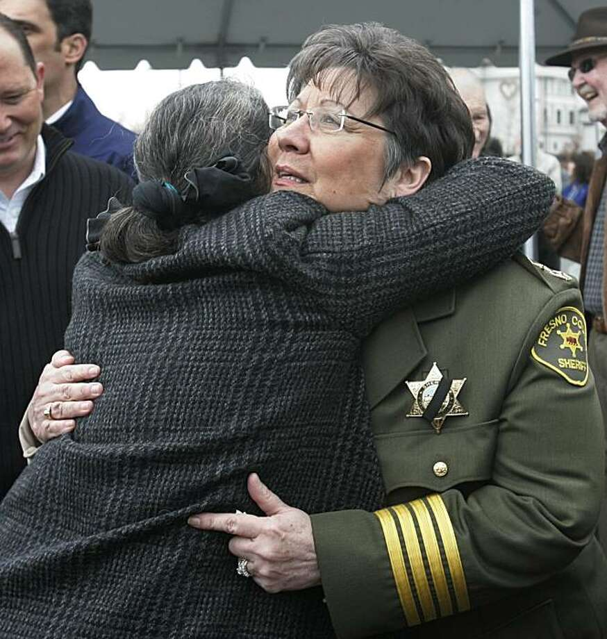 Fresno County Sheriff Margaret Mims, right, hugs a woman during a freeway dedication ceremony for Fresno County Sheriff's Deputy David Graves in Fresno, Calif., Friday, Feb. 26, 2010, who was killed in Nov. 1982. Mims talked during the dedication about asheriff's homicide detective who was killed on Thursday in a shootout while serving a search warrant at a mobile home. The suspect, who has not been identified, was also killed. Two other officers were wounded. Photo: Paul Sakuma, AP