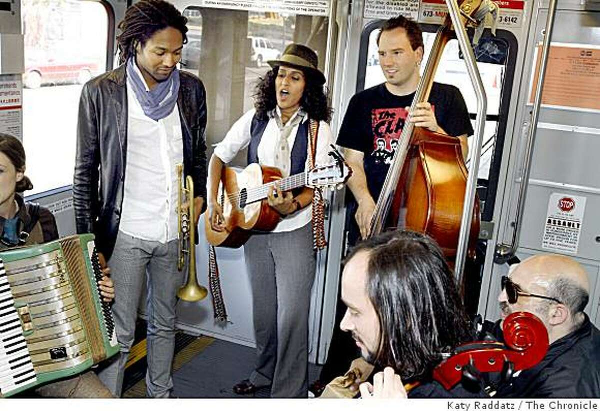 Rupa, leader of Rupa and the April Fishes, on guitar, with trumpet player Marcus Cohen on left and bass player Djordje Stijepovic on the right, with cello player Pawel Walerowski in foreground seated next to a transit passenger, on the N Judah streetcar in San Francisco, Calif. on Monday, Aug. 11, 2008.