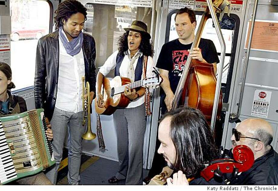 Rupa, leader of Rupa and the April Fishes, on guitar, with trumpet player Marcus Cohen on left and bass player Djordje Stijepovic on the right, with cello player Pawel Walerowski in foreground seated next to a transit passenger,  on the N Judah streetcar in San Francisco, Calif. on Monday,  Aug. 11, 2008. Photo: Katy Raddatz, The Chronicle
