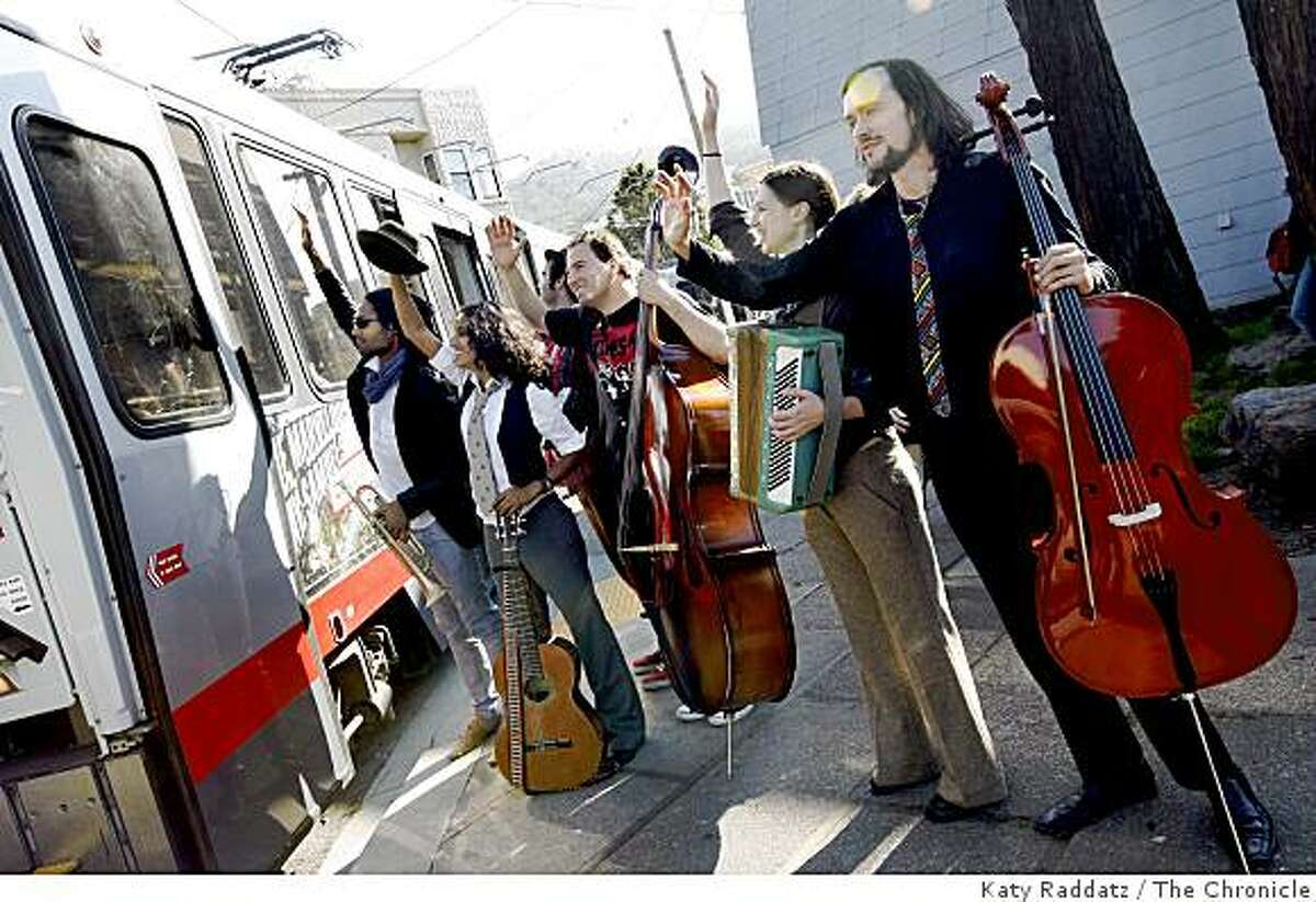 Marcus Cohen, left, Rupa, second from left, Aaron Kierbel, third from left, Djordje Stijepovic, fourth from left, Isabel Douglass, second from right, and Pawel Walerowski, right, all of Rupa and the April Fishes, who got their start playing on streetcars, wave goodbye to passengers who had listened to them play all the way from the Embarcadero on the N Judah streetcar, at Carl and Cole Streets in San Francisco, Calif. on Monday, Aug. 11, 2008.