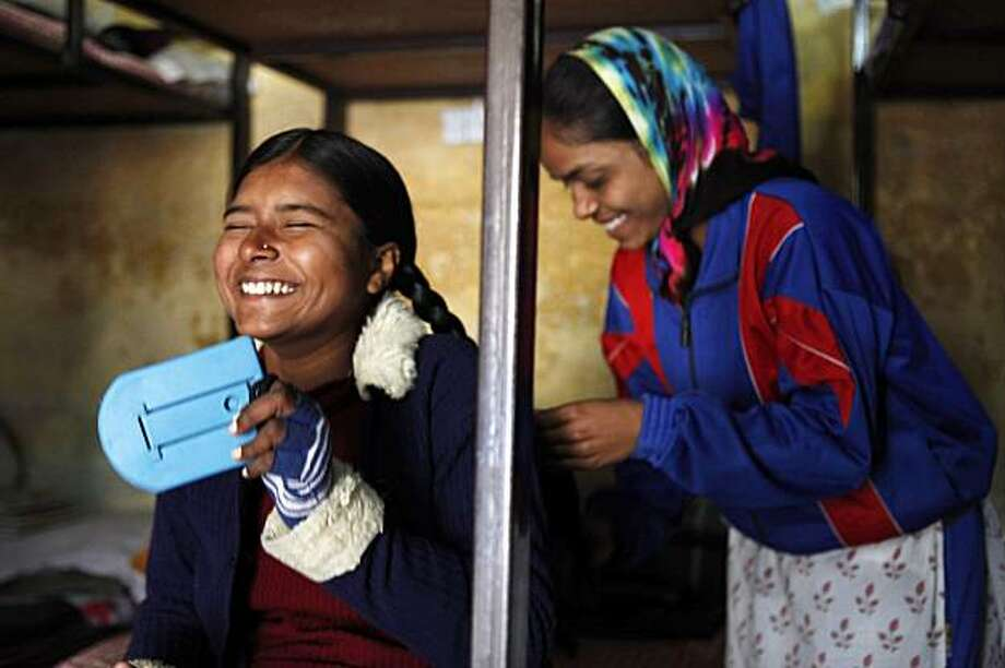 In this photo taken Thursday, Jan. 21, 2010, two unidentified students from the girls hostel at Akhil Bharatiya Mahila Ashram in Dehradun, India laugh together as they prepare for school in the morning. At the foothills of the Himalayas, the ashram is home to 50 girls from impoverished communities across India. The ashram gives them an education, housing, food, and Hindu religious instruction. They say that living in the girls hostel has given them the confidence that women can do anything that men can. Photo: Jacquelyn Martin, AP